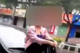بالفيديو...تشاجرت مع زوجها فجلست على غطاء المحرك طول الطريق