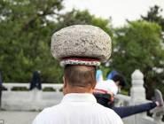 صيني يحمل حجراً ثقيلاً على رأسه ويسير به بشكل يومي بهدف خسارة وزنه الزائد